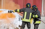 Постер, плакат: Two Firefighters In Action With Foam