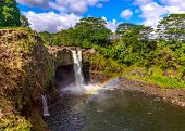 image of big-foot  - Waterfall with rainbow in Hawaii also know as Waianuenue Falls that flows 80 feet over a natural lava cave into a turquoise pool of water surrounded by dense forest - JPG