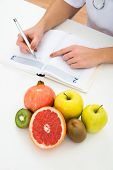 picture of prescription  - High Angle View Of Female Dietician Writing Prescription With Fruits On Desk - JPG