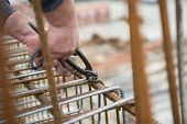 picture of concrete pouring  - Worker hands using steel wire and pincers to secure rebar before concrete is poured over it - JPG
