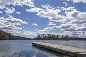 stock photo of dock a lake  - Dock stretches across Wawayanda Lake in early springtime - JPG