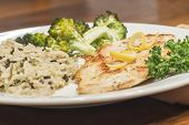 foto of crispy rice  - Crispy tender lemon chicken garnished with lemon twist with sides of herb wild rice and lemon broccoli - JPG