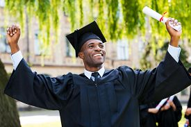 image of graduation gown  - Happy young African man in graduation gowns holding diploma and rising arms up while his friends standing in the background