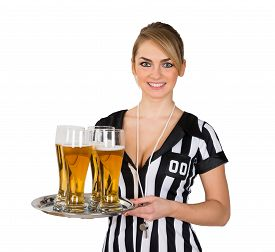 stock photo of referee  - Young Female Referee Holding Tray With Glass Of Beer Over White Background - JPG