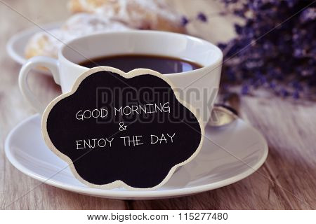 the text good morning and enjoy the day written in a thought bubble-shaped blackboard placed in a cu