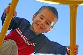 image of swingset  - a little boy playing on the playground with a blue sky background - JPG