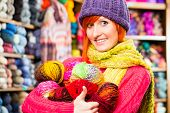 Постер, плакат: Young woman buying colorful wool and yarn for their hobby in a knitting shop