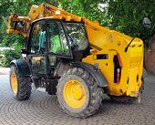 image of jcb  - Yellow construction vehicle turning into work site - JPG
