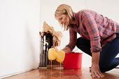 Worried woman mopping up water from a burst pipe with sponge poster