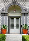 Elegant Home Front Door with gray wood arch and alternating brick work pattern