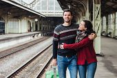 Romantic Couple Embrace At Railway Station, Say Good Bye To Each Other. Affectionate Wife Hugs Husba poster