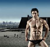 Retrato de moda sexy modelo masculino em cuecas pretas em cima do telhado com cidade no fundo