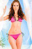 Vogue style photo of sensual young girl in pink bikini posing in summerhouse on beach.