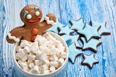 Blue glass mug with hot cocoa and marshmallows, homemade gingerbread man, handmade ginger cookies on poster