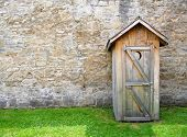 image of outhouses  - Image of a rustic outhouse with a vintage stone wall - JPG