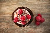 Tasty chocolate cupcake on wooden table poster