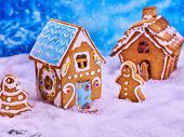 Christmas cookies gingerbread houses and gingerbread man next to them in snow. Village Xmas sweet fo poster