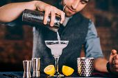 Professional Bartender Pouring Margarita Cocktail With Strainer And Cocktail Tools poster