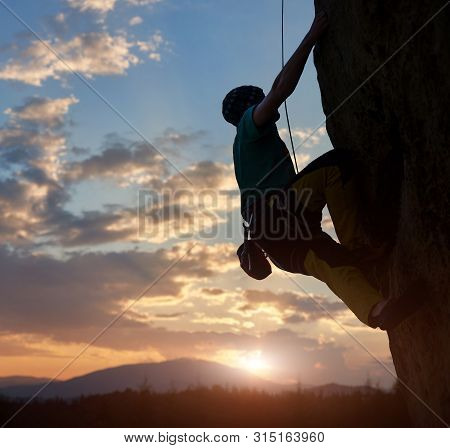 poster of Silhouette Of Man Climbing On Rock. Climber Training On Natural Relief. Extreme Sport. Active Recrea
