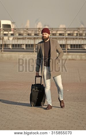 poster of Carry Travel Bag. Man Bearded Hipster Travel With Luggage Bag On Wheels. Traveler With Suitcase Arri