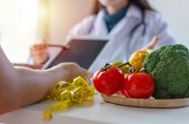 Focus Fresh Vegetables And Fruits With Nutritionist Female Doctor Or Medical Using Tablet And Talkin poster
