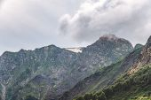 Clouds And Fog On The Slopes Of Mountain Ranges With Snowy Peaks In Summer. High Mountains With Gree poster