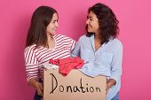 Close Up Portrait Of Two Girls Volunteering, Women Holding Box With Clothes For Poor People, Attract poster