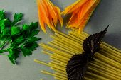 Spaghetti Sticks, Parsley And Sweet Basil Leaves, Orange Flowers On Gray Kitchen Table Background. F poster