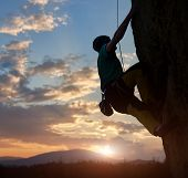 Silhouette Of Man Climbing On Rock. Climber Training On Natural Relief. Extreme Sport. Active Recrea poster