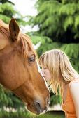stock photo of horse riding  - young blond woman kissing a brown horse - JPG