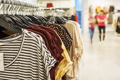 Fashionable Clothes On Hangers In A Store For Youth. Shirts, Blouses, Bright T-shirts On A Hanger. S poster