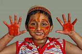 Young happy Asian Bengali Boy Playing Holi, Smiling With Colors On Face And Hands, cap on head,