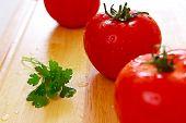 Drei frische Tomaten mit Wassertropfen auf Sie