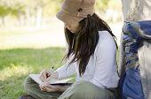 Escritura en diario de viaje de la mujer joven