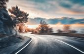 Mountain Road At Sunset With Motion Blur Effect. Asphalt Road And Blurred Background With Rocks, Blu poster