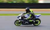 Racing Bike Rider In Helmet Racing At High Speed On Race Track With Motion Blur poster