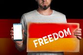 A Man With A Cardboard And A Phone In His Hand. The Flag Of Germany. Concept Of Freedoms And Human R poster