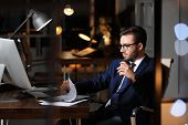 Concentrated Young Businessman Working In Office Alone At Night poster