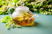 Fresh Aromatic Tea With Melissa Mint Leaves Glass Teapot On A Rustic Background. Healing Herbal Drin poster