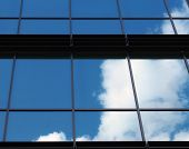 Clouds And Bright Blue Sky Reflected In The Square Mirrored Windows Of A Modern Commercial Office Bu poster
