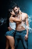 Sexy And Wet Woman Hugging Handsome And Muscular Boyfriend Under Raindrops On Black poster