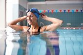 Female Swimmer Wearing Hat And Goggles Training In Swimming Pool poster