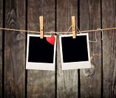 Blank instant photos and small red paper heart hanging on the clothesline. On old wood background.