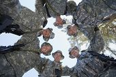 Low angle view of happy group of soldiers forming a huddle