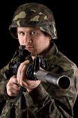 Soldado vigilante con el objetivo de M16 en estudio