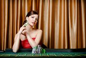 stock photo of roulette table  - Portrait of female gambler sitting at the casino table with chips in hand - JPG