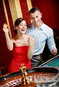Happy couple playing roulette wins at the casino club