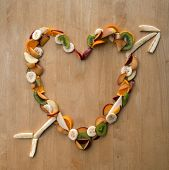 stock photo of satsuma  - Sliced Fruit in Heart Shape with Arrow for Valentine - JPG