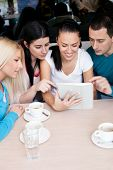 group of teenagers using tablet touch at cafe
