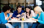 Group of teenagers students on lunch in restaurant